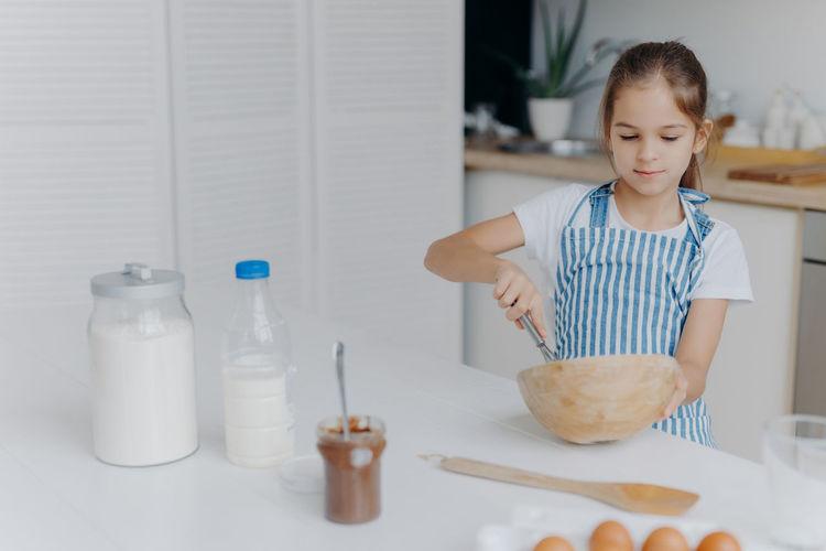 Smiling girl preparing food at home