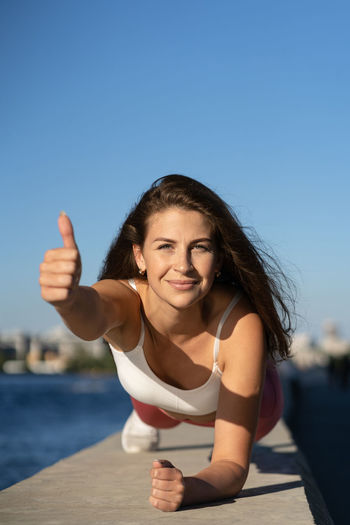 Portrait of young woman against clear blue sky