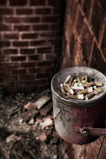 High Angle View Of Cigarettes On Bin Hanging At Wall