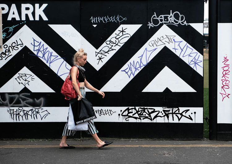 Full length of young woman standing against graffiti