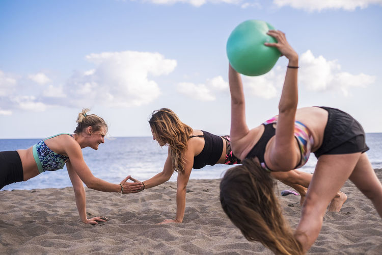 Young Friends Exercising At Beach