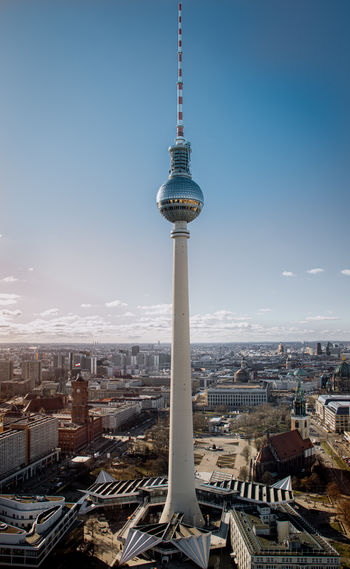 Television tower in city against sky