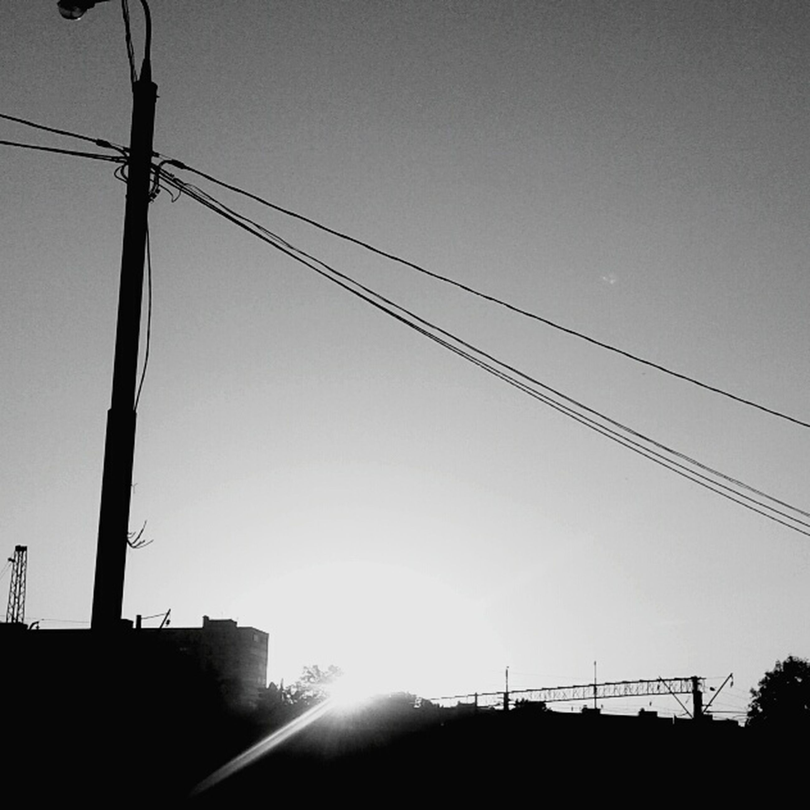 power line, low angle view, clear sky, silhouette, electricity pylon, cable, electricity, power supply, connection, fuel and power generation, built structure, sunset, sun, copy space, technology, building exterior, architecture, sky, sunlight, power cable