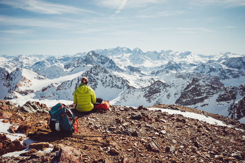 Rear view of people sitting on snowcapped mountains against sky
