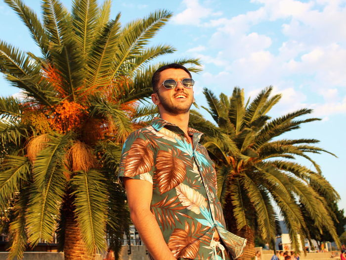 Low angle view of man wearing sunglasses standing against palm trees
