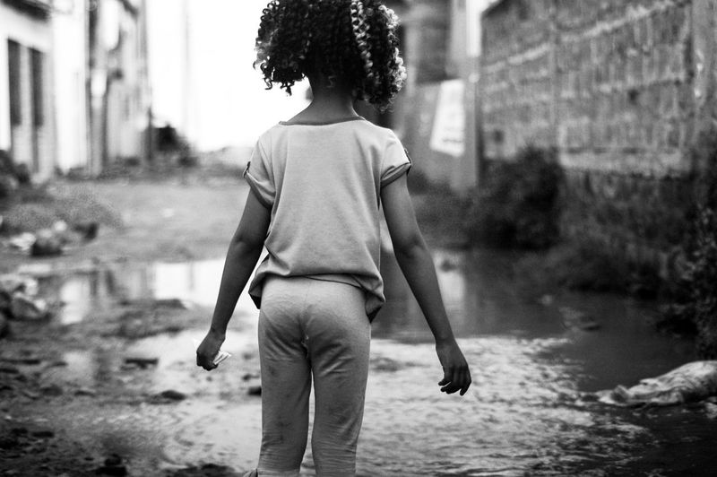 Rear View Of Girl Standing By Puddle In City