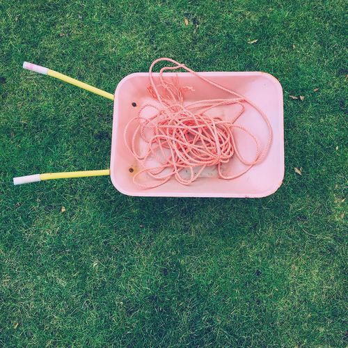 Directly above shot of ropes in wheelbarrow on grassy field