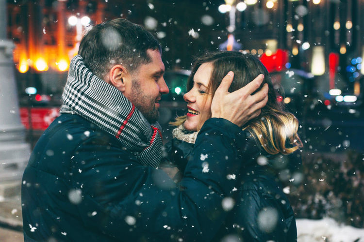 Real young couple walking together in night city under snow, kissing and smiling, winter romance, lifestyle Winter Cold Temperature Two People Love Emotion Men Warm Clothing Snow Positive Emotion Night Celebration Christmas Adult Couple - Relationship Holiday Clothing Snowing Togetherness Males  Scarf Outdoors