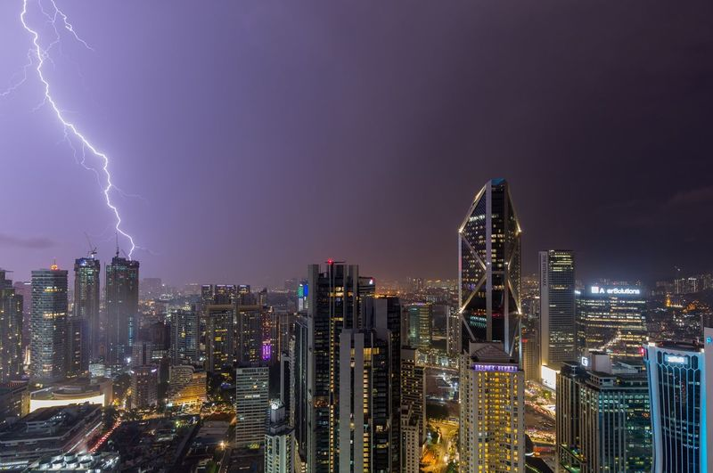 Thunder lightning strike on the building tower during night from high angle view Cityscape Striking Thunderstorm Building Exterior City Architecture Built Structure Night Skyscraper Office Building Exterior Illuminated Building Cityscape Modern Sky Urban Skyline Residential District Landscape Office Nature City Life Travel Destinations No People
