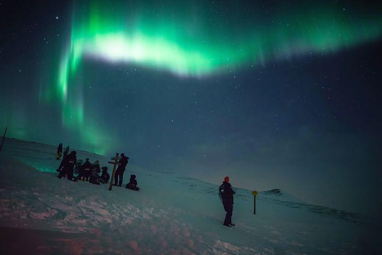 People on snowy mountain against idyllic aurora