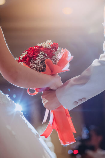 The hand of the bride and groom. Red roses bouquet at a party celebrating the wedding with beautiful bokeh background. Beauty Bouquet Love Newlywed Roses Celebration Couple Groom Happiness Happy Red Bridal Bouquet Bride Close-up Flower Hand Marriage  Marry People Wedding Day First Eyeem Photo