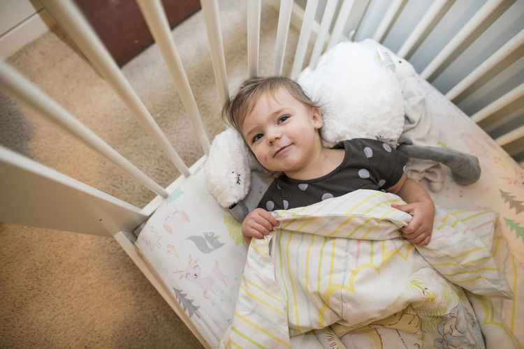 High angle view of cute baby lying on bed at home