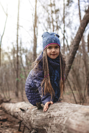 Portrait of girl wearing sunglasses on tree trunk