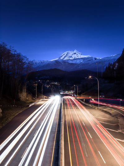 Light trails on road in city against sky at night