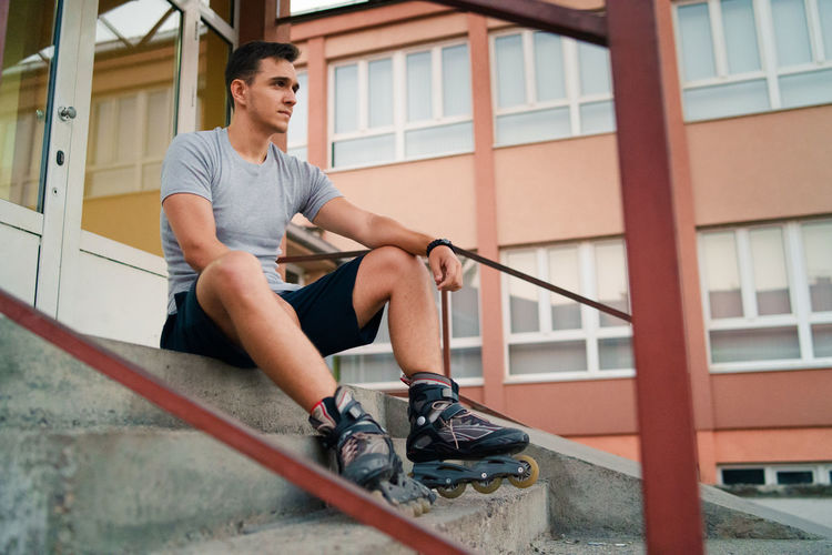 Man looking away while sitting on staircase against building