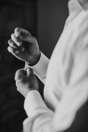 Midsection of man holding cuffs