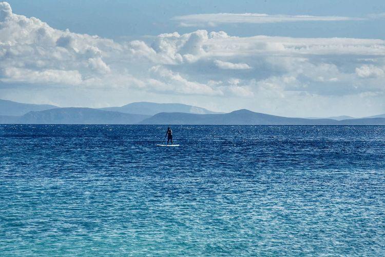 Man paddleboarding on sea against sky