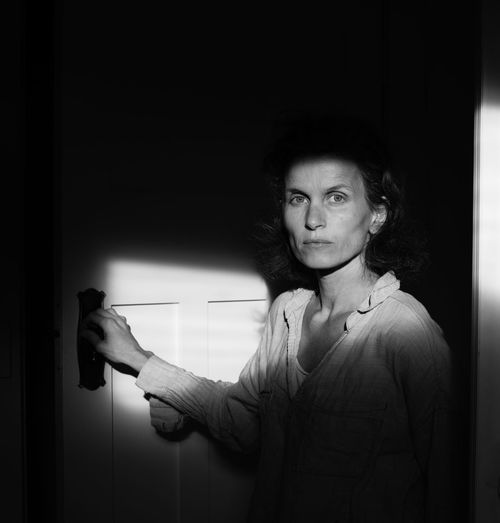 Woman by door with harsh light (black and white) Woman Black And White Day Indoors  Lifestyles One Person People Real People Shadow
