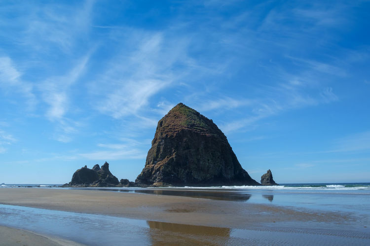 Rock formations on beach against blue sky