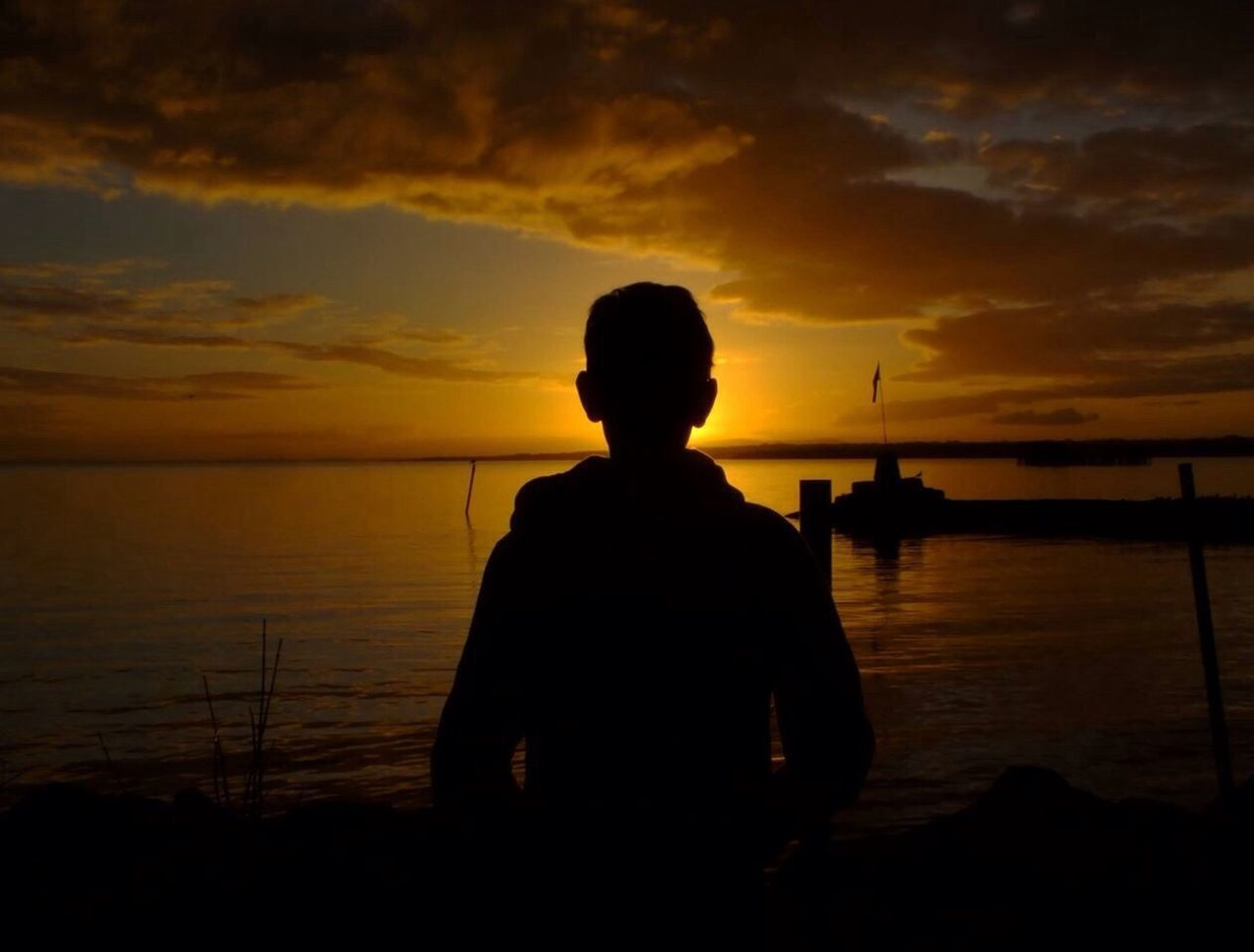 Silhouette Rear View of Boy Standing At Beach During Sunset