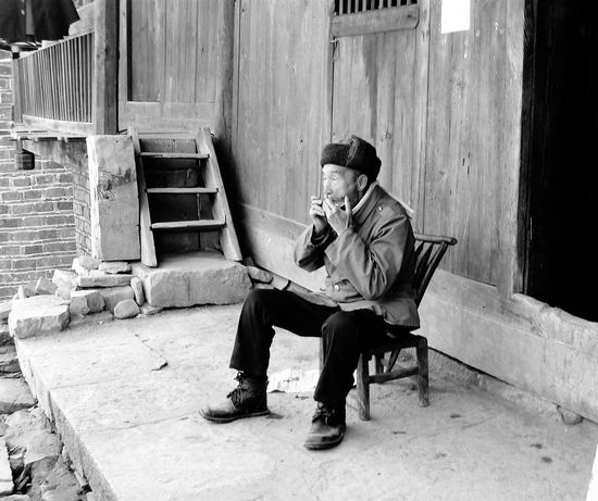 An extremely pleasant villager playing with his harmonica outside his home in China. China China Trip Beautiful People Travel Photography Black And White Black And White Photography Portrait Of A Man  Eyeemphoto Monochrome Photography