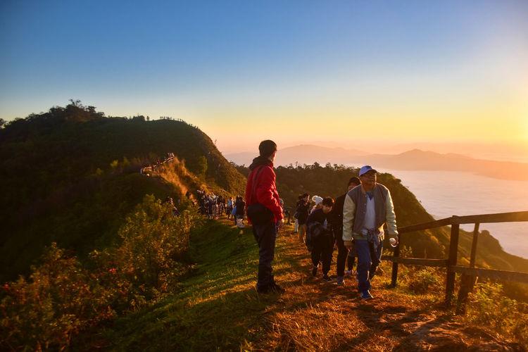 People standing on ridge during sunset