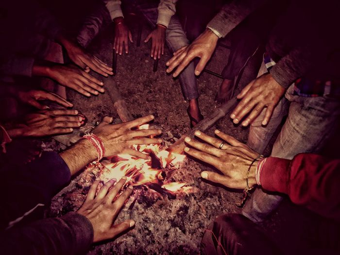 Male friends warming hands over campfire