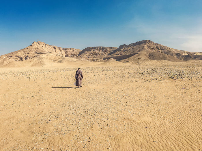 Rear view of man walking by mountains on desert against sky