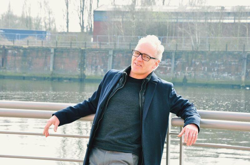 Portrait of mature man at railing against lake
