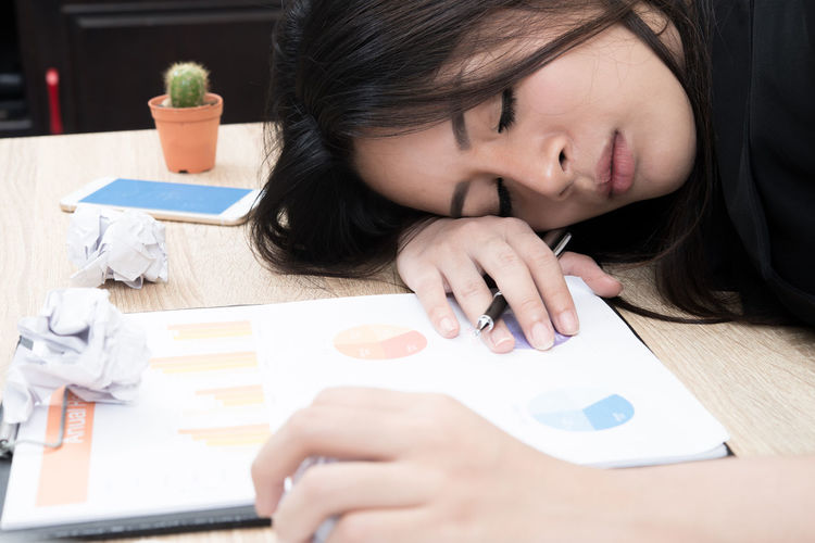 Close-Up Of Young Businesswoman Napping On Table In Office