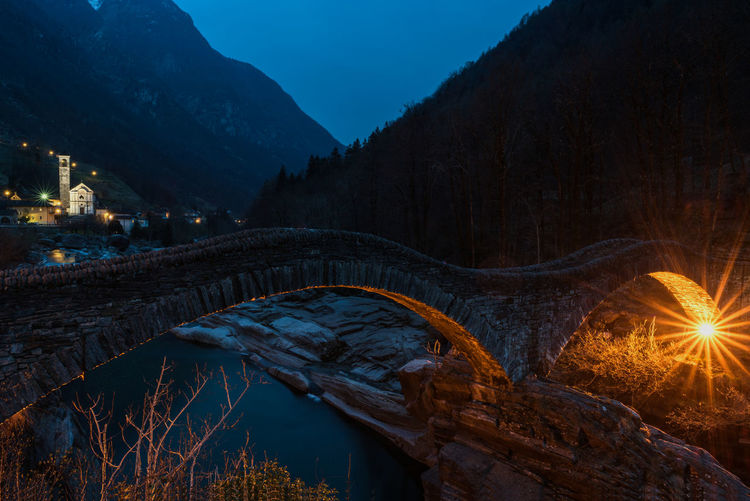 Illuminated bridge by mountains against sky at night