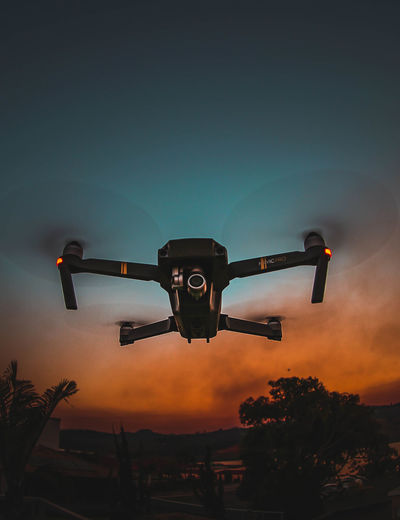 Low angle view of drone flying against sky at sunset
