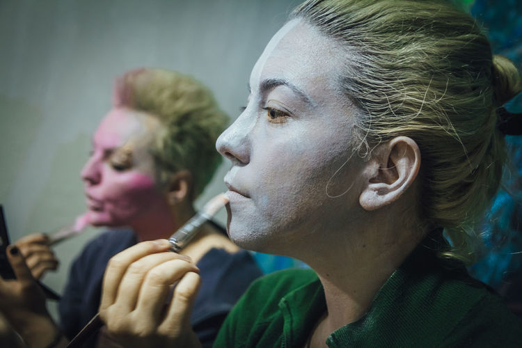 Two girls getting ready in teenage bedroom, putting makeup on, Creative body paint, Halloween Headshot Portrait Close-up Looking Side View Adult People Women Indoors  Blond Hair Focus On Foreground Looking Away Lifestyles Young Adult Hair Real People Leisure Activity Hairstyle Profile View Contemplation Human Face Beautiful Woman Makeup Celebration Facepaint