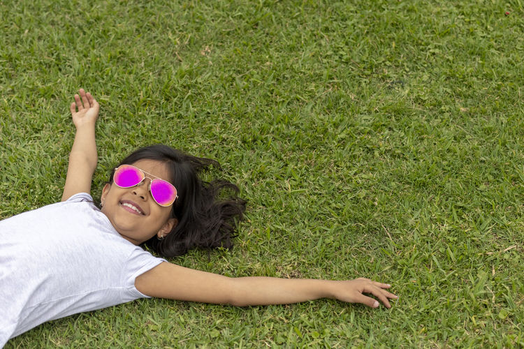 Beautiful girl with sunglasses lying on the grass Lying Down Grass Relaxation One Person Leisure Activity Plant Women Young Adult Human Arm Day Field Lying On Back High Angle View Nature Lifestyles Limb Sunglasses Arms Raised Smiling Fashion Outdoors Human Limb
