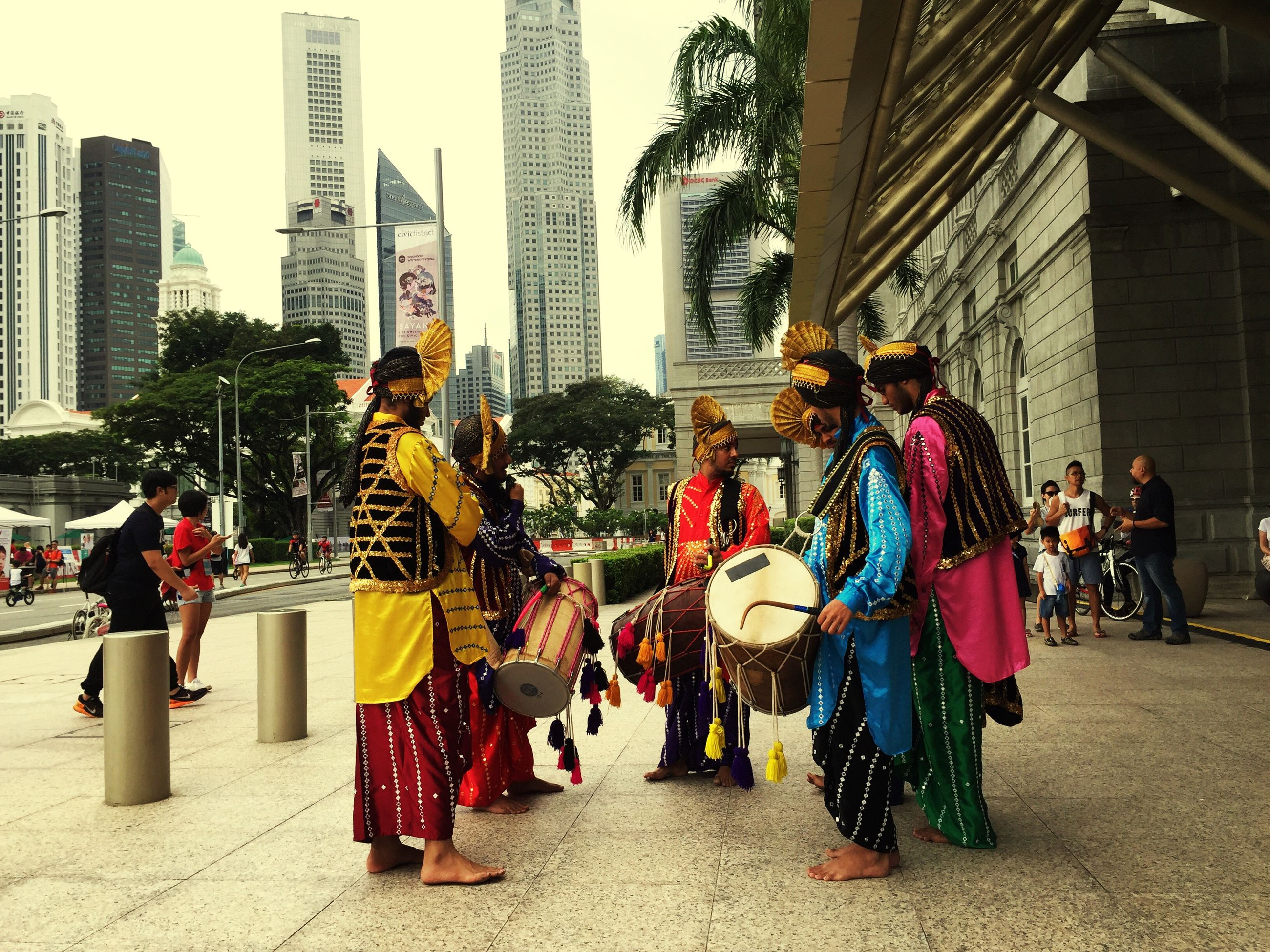 real people, architecture, built structure, full length, celebration, building exterior, medium group of people, city, music, traditional clothing, musical instrument, women, day, outdoors, men, parade, uniform, crowd, people, headwear, adults only, adult