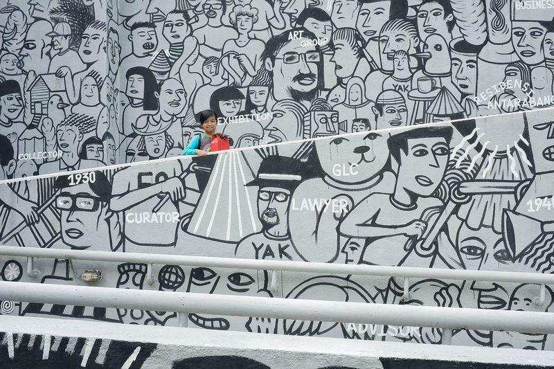 Woman standing against graffiti wall