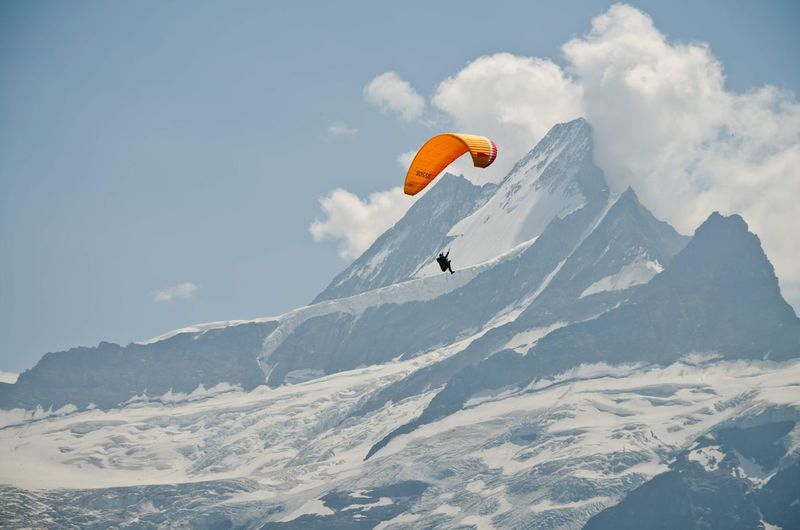 People paragliding over snowcapped mountain against sky