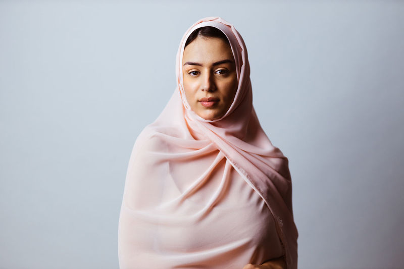 Portrait of young woman wearing hijab standing against gray background