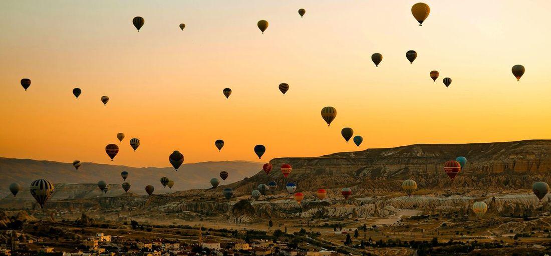 Hot air balloons flying over cappadocia against orange sky