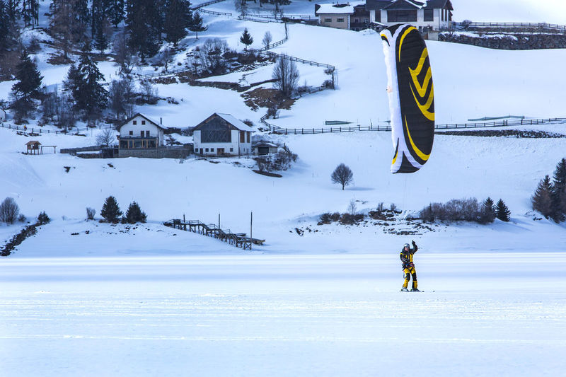 Man kiteboarding on snow covered field