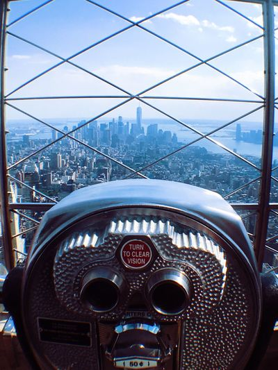 Close-up of coin-operated binoculars at empire state building against sky