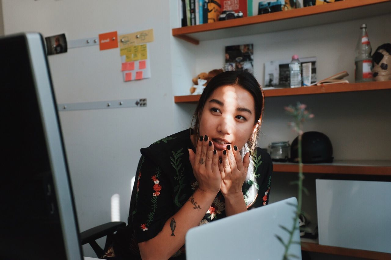 Young Woman Sitting With Laptop And Computer At Office