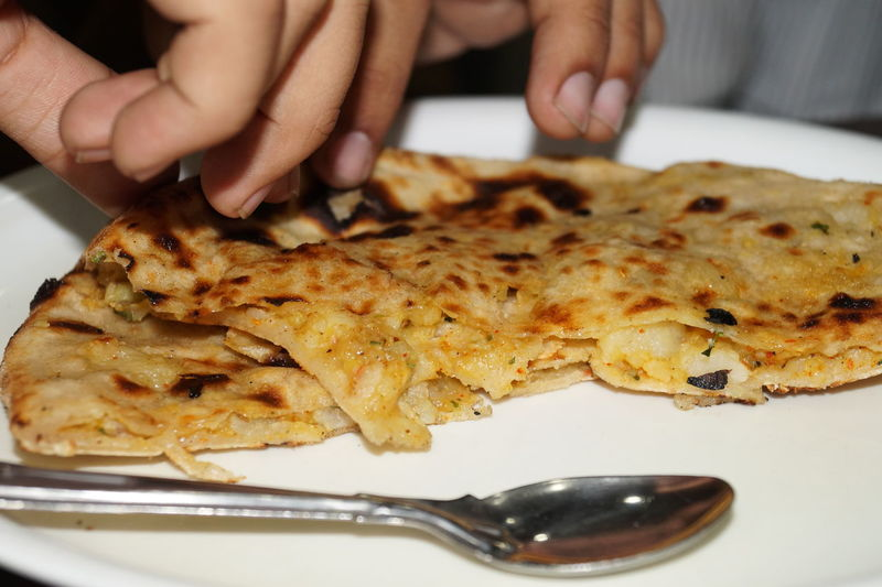 Cropped image of person eating paratha in plate
