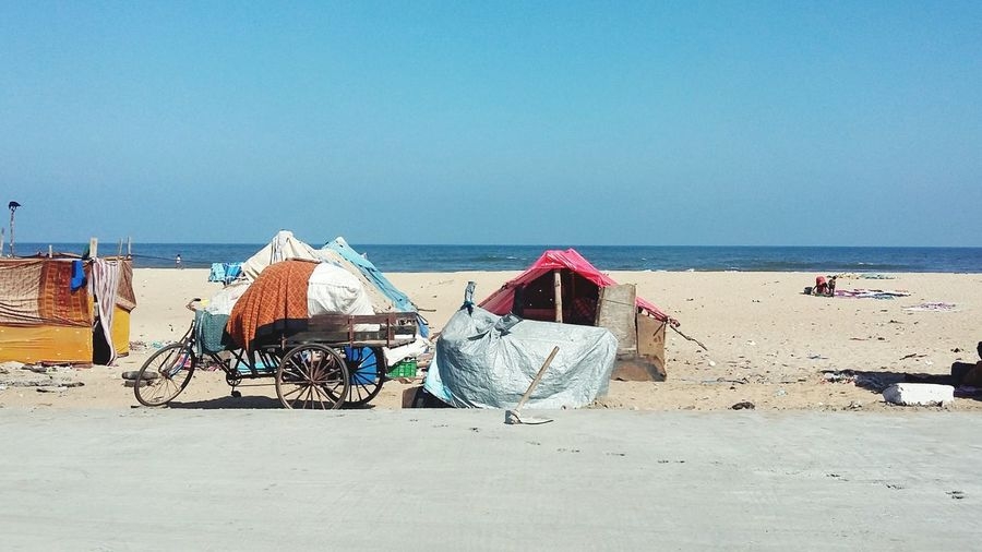 Bicycle cart parked by hut at beach against clear sky