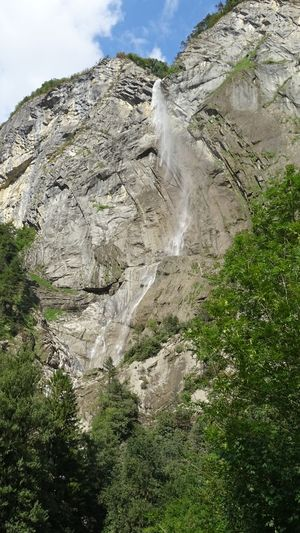 Low angle view of waterfall amidst rocks against sky