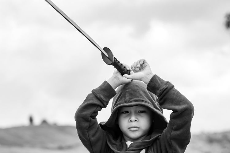 Portrait Of Boy Holding Sword Against Sky