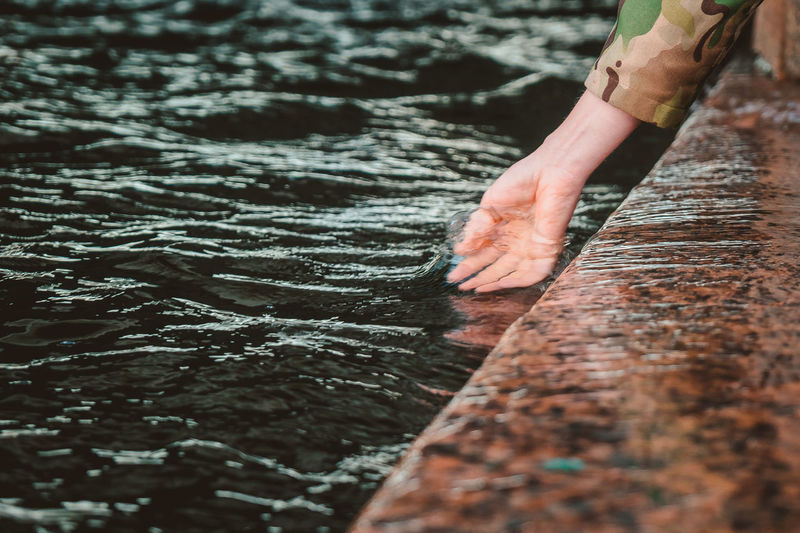 Cropped image of hand on water