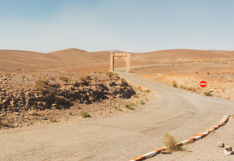 Portal Another Dimension Arid Climate Canyon Day Desert Desert Landscape Dirt Road Environment Gate Gateway Landscape Nature New Realms No People Portal Portal To Another World. Portrait Remote Road Sahara Scenics Stop Tor Travel Winding Road