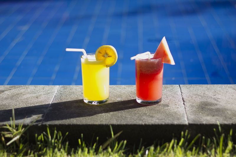 Close-up of drinks by the pool