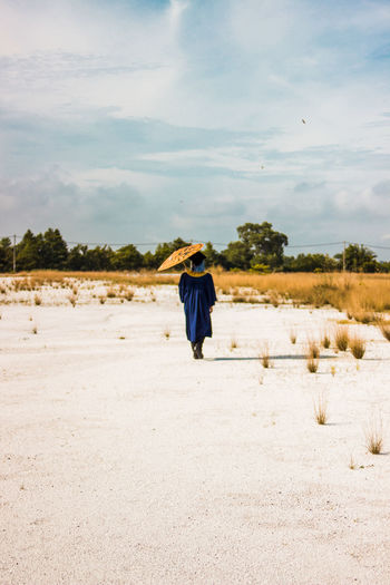 Rear view of man walking on land against sky during summer